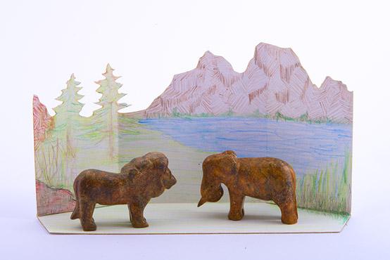 Un lion et un éléphant sculptés sur de la pierre à savon avec leur habitat naturel dessiné en arrière plan