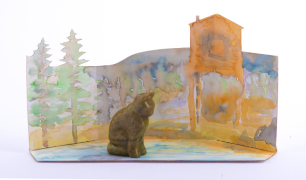 Cat made with soapstone with background drawn/ painted in the background with trees and house