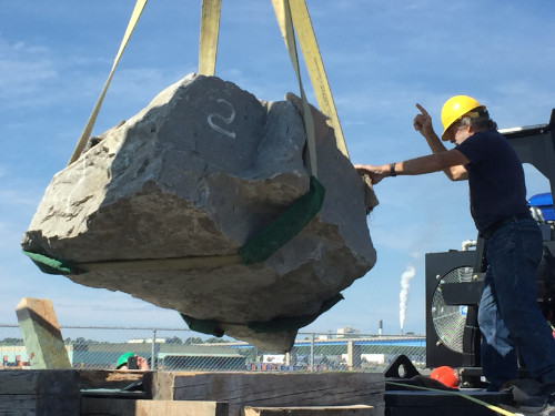 Rock being moved, a man supervising the operation