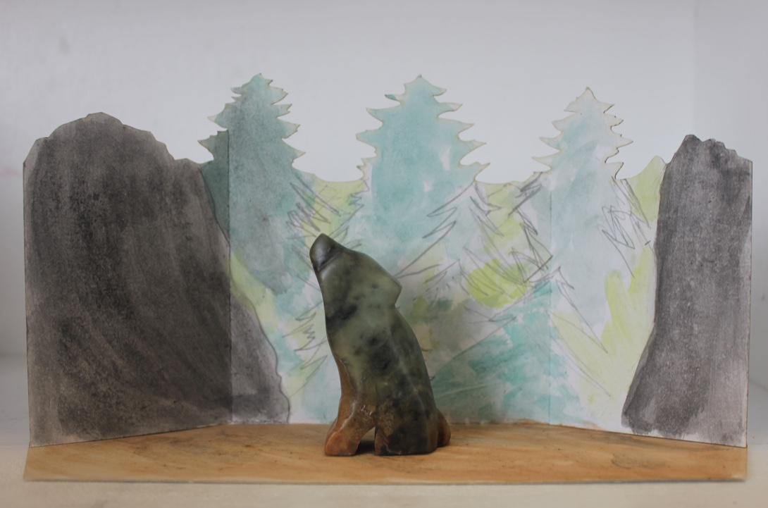Wolf made with soapstone with natural habitat drawn/ painted in the background with trees and mountains