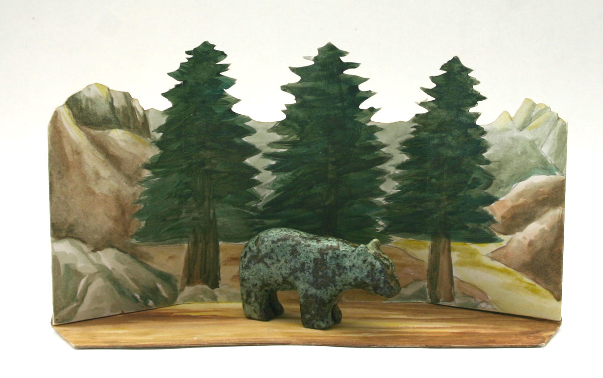 Bear made with soapstone with natural habitat drawn/ painted in the background with trees and mountains