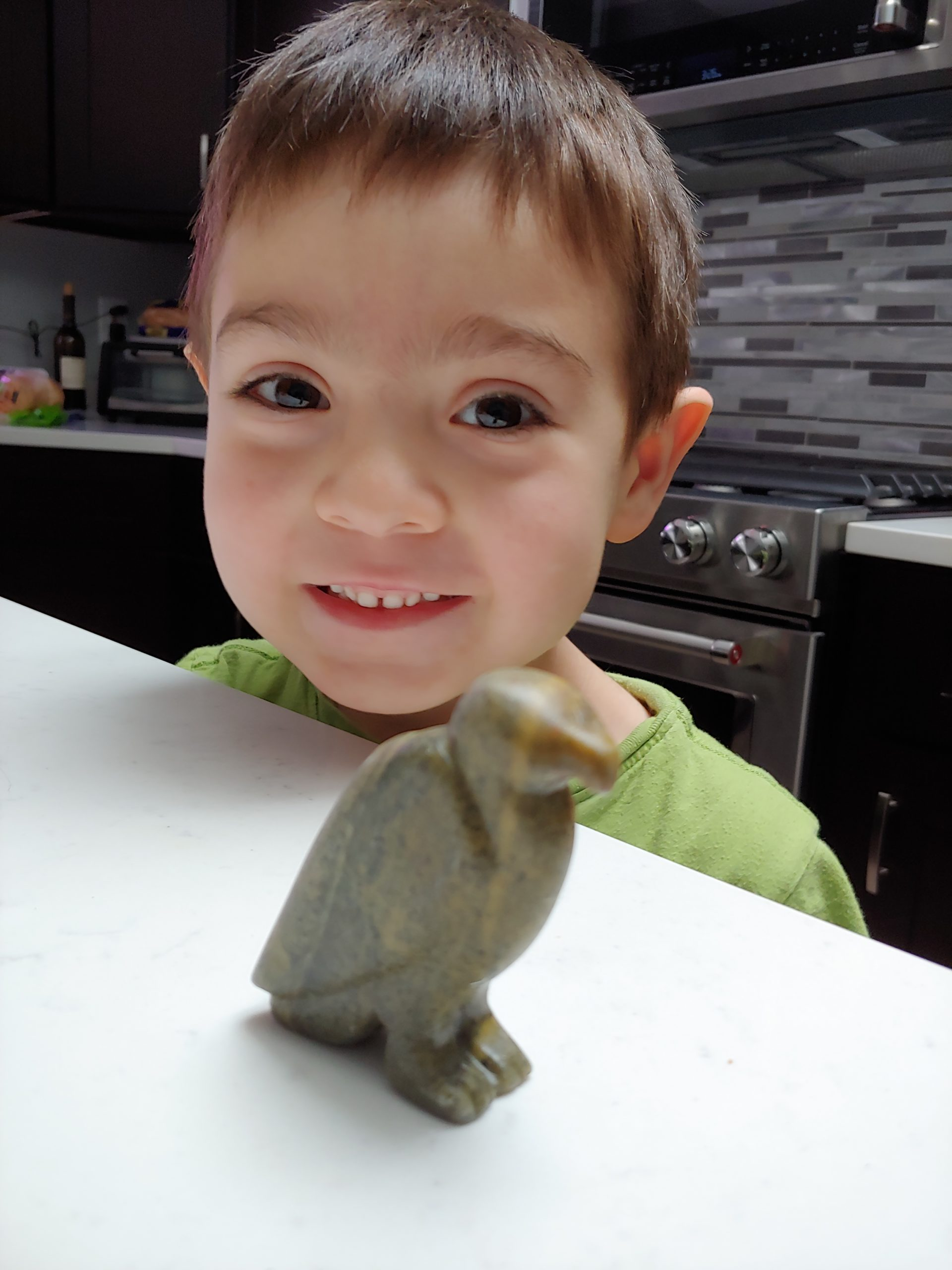 Young boy with a eagle carved from soapstone