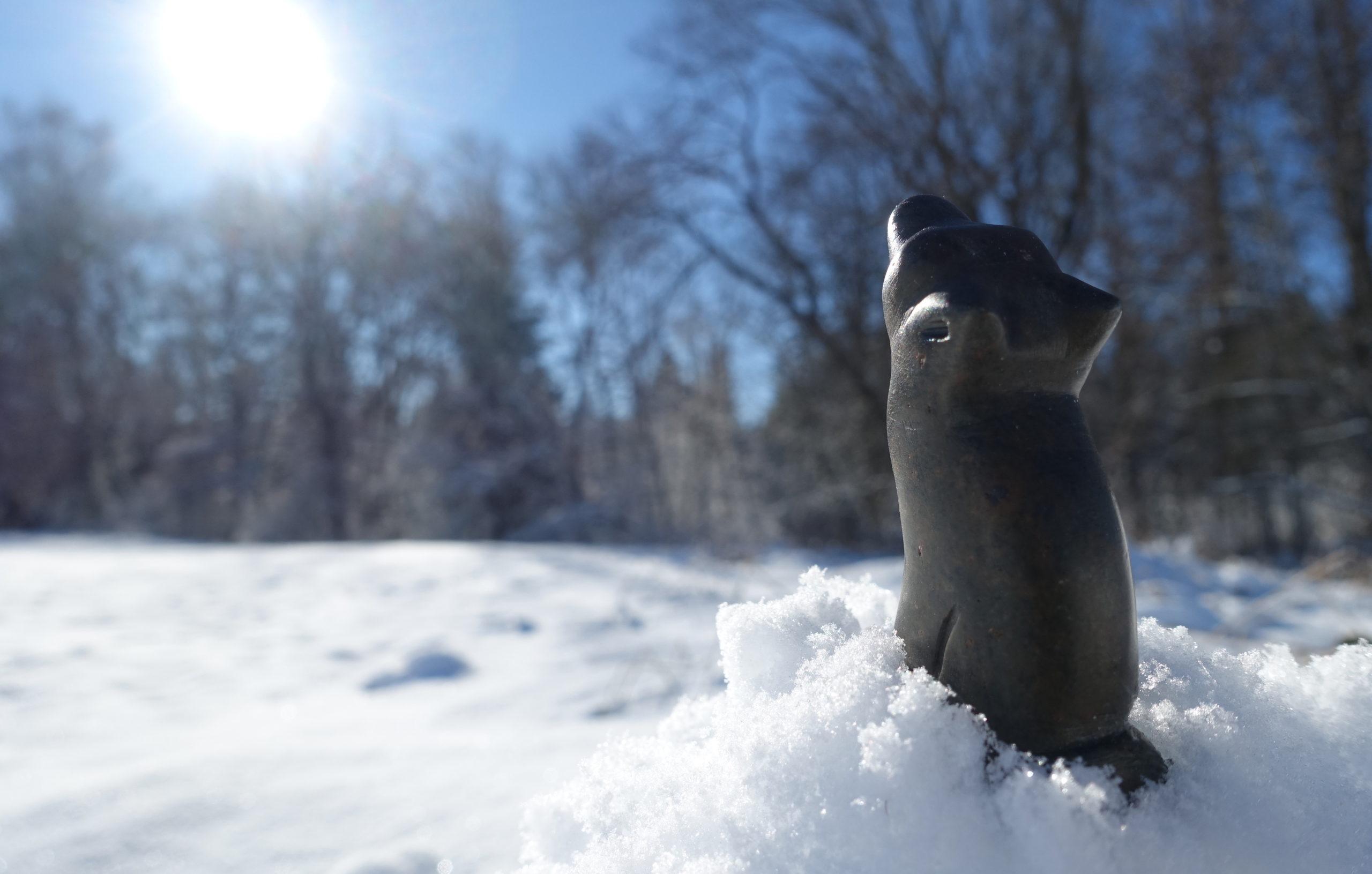 Un loup sculpté sur de la pierre à savon sur de la neige sous le soleil