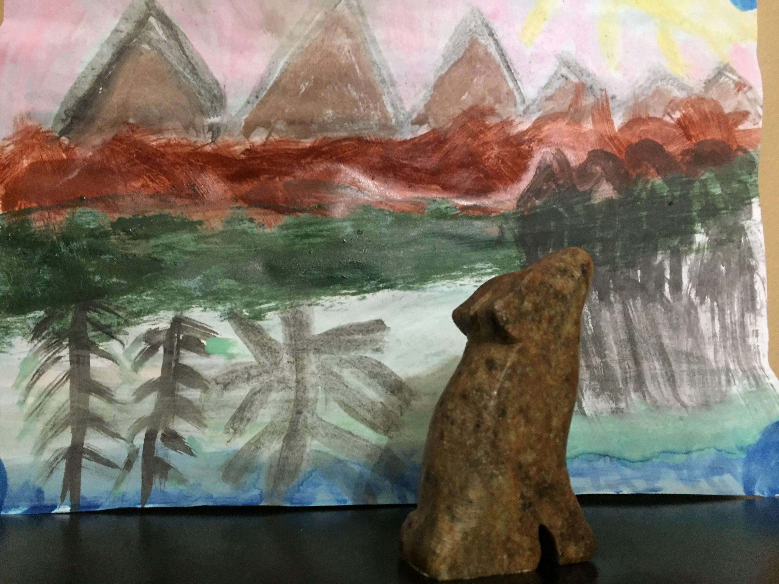 Un loup sculpté sur de la pierre à savon avec un fond peint avec des montagnes
